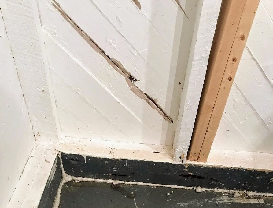she shed corner with spray foam sealant, sistered wall supports and wood slat walls