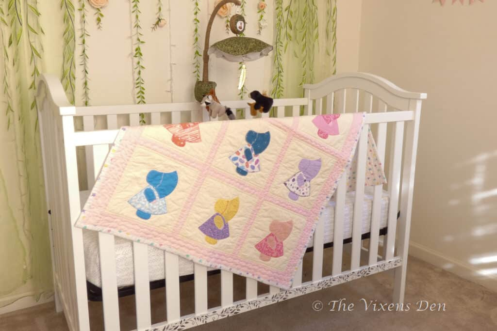 painted and stenciled crib shown with handmade quilt and mobile