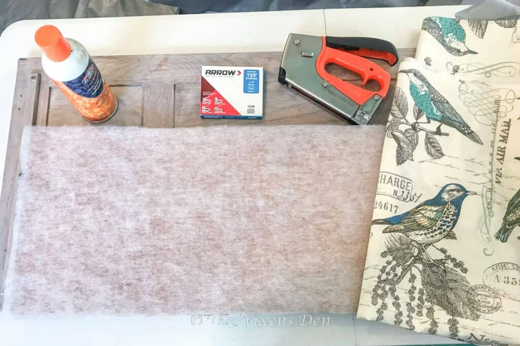 corkboard with luan backing and quilt batting applied and additional supplies ready to use: spray adhesive, staple gun, staples and fabric