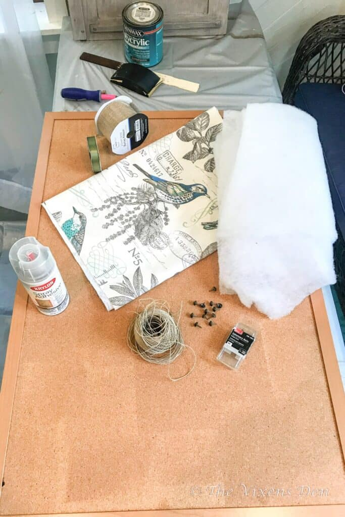 used corkboard with supplies: fabric, spray adhesive, ribbon, quilt batting, upholstery nails and jute cord