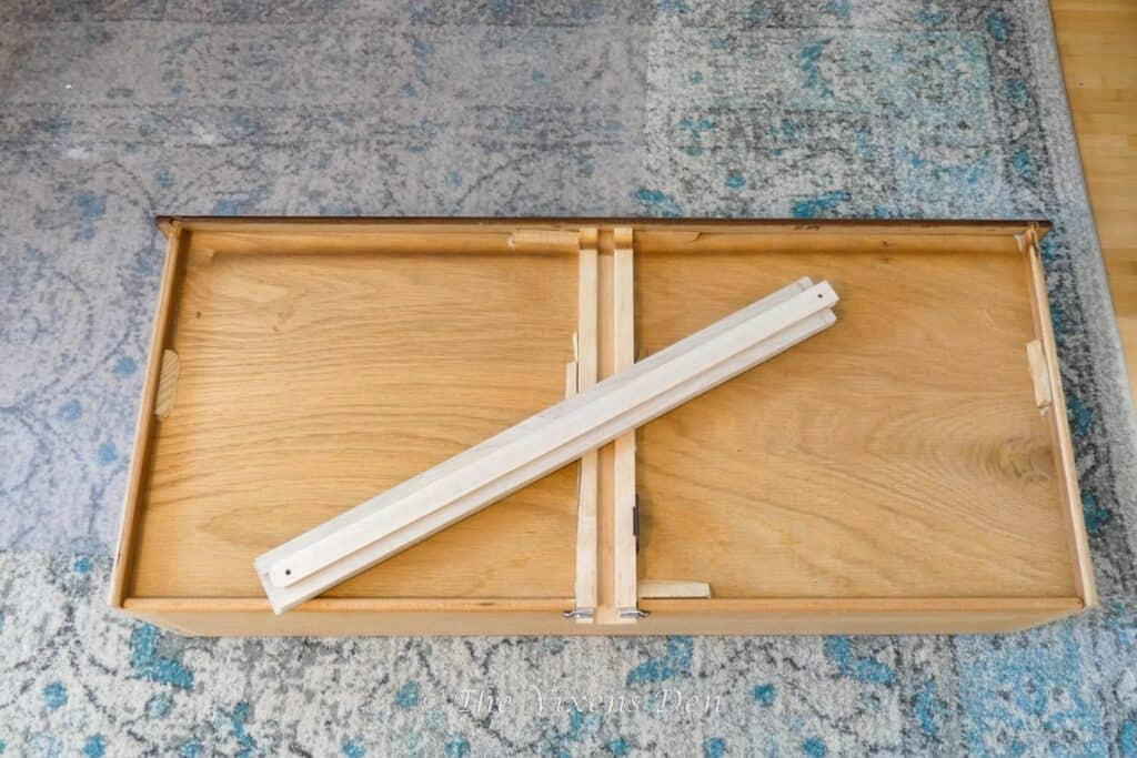 bottom of a drawer with replacement wood drawer slide laying at an angle