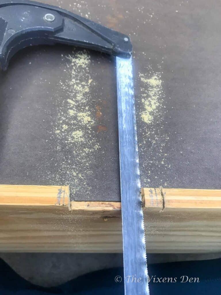 hacksaw cutting into wood drawer bottom