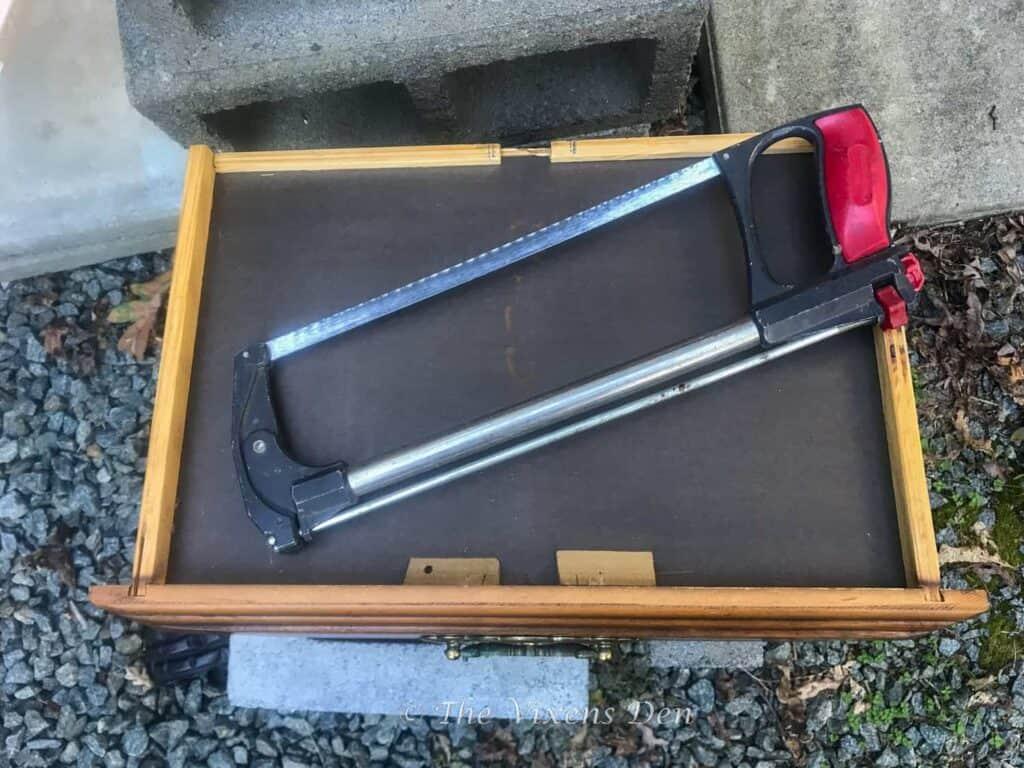 hacksaw laying on a drawer bottom