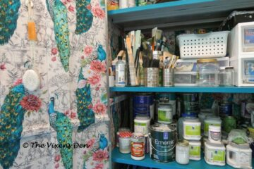 close up of metal garage cabinet lined with peacock fabric and paint supplies
